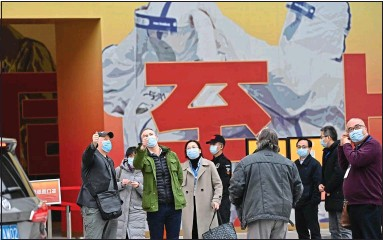 ??  ?? PROPAGANDA? The WHO inspectors gathered outside an exhibition on Covid-19 in Wuhan yesterday