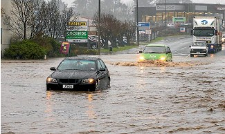 ?? PHOTO: STUFF ?? Cars drive through a flooded area of State Highway 1 in Timaru yesterday.