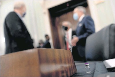 ?? PHOTOS BY THE ASSOCIATED PRESS ?? An example of the Pfizer COVID-19 vaccine vial is visible on a desk before FedEx executive Richard Smith (left), andWesley Wheeler with United Parcel Service during a Senate Transportation subcommittee hybrid hearing Thursday on transporting a coronavirus vaccine. Pfizer's vaccine cleared another key hurdle Thursday, and shots could begin in days.