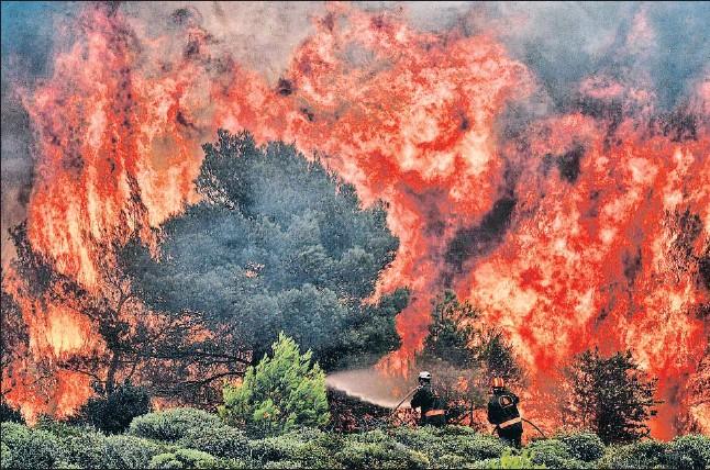 ?? ANGELOS TZORTZINIS / AFP ?? Los bomberos, como estos que trabajan en el incendio de Kinetia, cerca de Atenas, hicieron frente a rachas de viento de hasta 100 kilómetros por hora