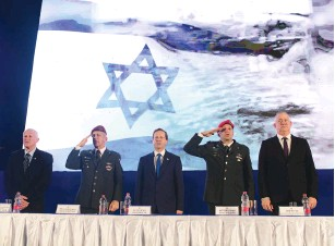 ?? (Tomer Neuberg/Flash90) ?? PRESIDENT ISAAC HERZOG, Defense Minister Benny Gantz and IDF Chief of Staff Lt.-Gen. Aviv Kohavi stand at attention at a graduation ceremony at the National Security College in Glilot earlier this week.