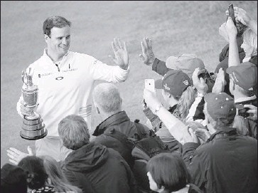 """?? Matthew Lewis Getty Images ?? FORTUNATELY for Zach Johnson, the Claret Jug can be held in one hand, leaving the other free to high- five spectators on a """"victory lap"""" along 18th fairway to celebrate his second major title. He also won 2007 Masters."""
