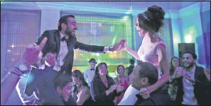 ?? THE ASSOCIATED PRESS ?? An Israeli couple, Simon David Benhamou and Noemie Azerad, grasp each other's hands on the shoulders of groomsmen during their wedding party at a hotel in Dubai.