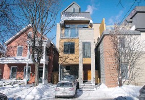 """??  ?? Manufactured stone, traditional cedar and a small veranda with columns help connect the home with its older surroundings. """"We wanted to respect the character of the neighbourhood,"""" says Delahousse. Visible are the dual windows of the second-floor..."""