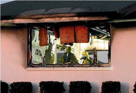 ?? HELEN NICKISSON/STUFF ?? Firefighters work in the kitchen of a Witherlea home in Blenheim, where a blaze caused severe damage last week.