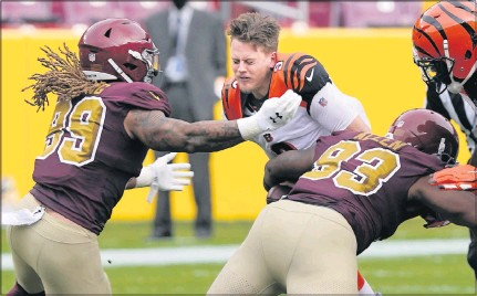 ?? THE ASSOCIATED PRESS ?? Cincinnati quarterback Joe Burrowloses his helmet as he is tackled byWashington defensive tackle Jonathan Allen (93) and defensive end Chase Young in the first half at FedEx Field in Landover, Md.