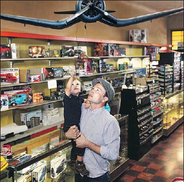 ?? Photographs by Dania Maxwell Los Angeles Times ?? COLBY GOMEZ, 2, and dad Tim Gomez, the great-grandson and grandson of Evett's Model Shop's owner.