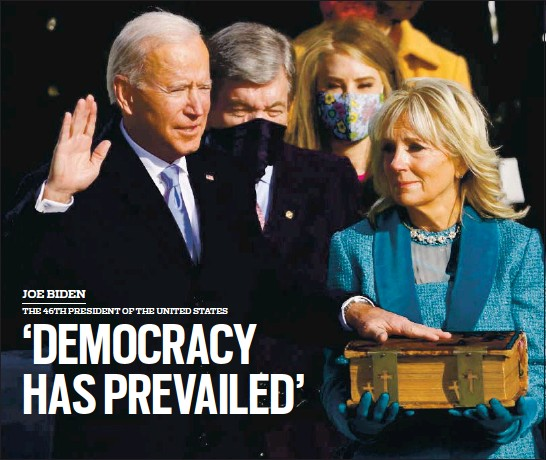 ?? ANDREW HARNIK — POOL/GETTY IMAGES ?? Joe Biden is sworn in as the 46th president of the United States by Chief Justice John Roberts as his wife, Jill Biden, holds the 19th-century family Bible during the 59th presidential inauguration at the U.S. Capitol in Washington, D.C., on Wednesday.