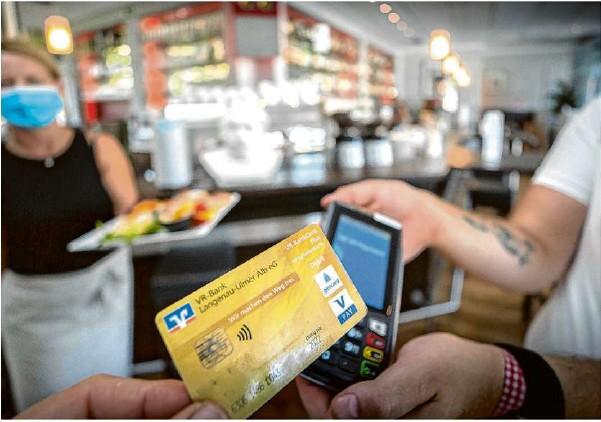 ?? Foto: Volkmar Könneke ?? Scheine und Münzen sind passé. Als erstes Ulmer Café hat das Einstein komplett auf bargeldloses Zahlen umgestellt.