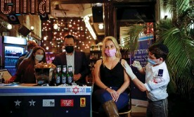 ?? Photograph: Corinna Kern/Reuters ?? A woman gets her Covid vaccination – and a free drink as an incentive – at a bar in Tel Aviv, Israel.