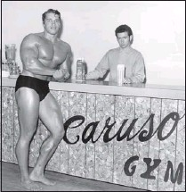 ?? COURTESY OF JIMMY CARUSO ?? Caruso photographed Arnold Schwarzenegger at his gym in the late 1960s. Caruso's son Gino is behind the counter.