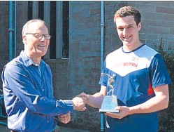 ??  ?? George Evans receives the trophy from Sandy Sutherland, who was coached by Mr Dalrymple.