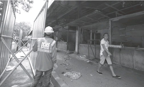 ?? BING GONZALES ?? CONSTRUCTION workers set up the fence around the old Agdao Public Market as they prepare for its demolition to give way for the construction of a modern building.