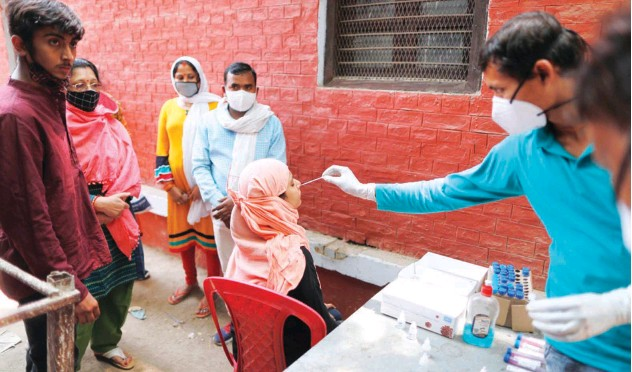 ?? Associated Press ?? ↑ A health worker takes a swab sample to test for virus in Prayagraj on Saturday.