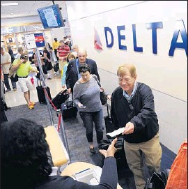 """?? John Amis Associated Press ?? DELTA says the number of miles needed to book a f light may rise based on destination, demand and """"other considerations."""" Above, passengers board in Atlanta."""