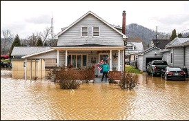 ?? RYAN C. HEMENS / LEXINGTON HERALD-LEADER ?? Catherine Castle stands on the porch of her home in downtown Paintsville, Ky., as floodwaters approach on Monday. Heavy thunderstorms pounded parts of Appalachia, leading to multiple water rescues.