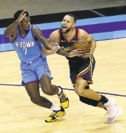 ?? Bob Levey / Getty Images ?? Houston's Armoni Brooks tries to keep his hand in while guarding a driving Stephen Curry.