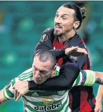 ?? PHOTO: REUTERS ?? Close contact . . . AC Milan's Zlatan Ibrahimovic gets to grips with Celtic's Scott Brown in yesterday's match at Celtic Park, in Glasgow.