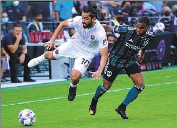 ?? SAMUEL GRANDSIR, Lynne Sladky Associated Press ?? right, battles Inter Miami midfielder Rodolfo Pizarro for the ball during the first half of L.A.'s 3-2 victory that made Greg Vanney a winner in his Galaxy coaching debut in Fort Lauderdale, Fla.