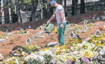 ??  ?? WA­TER­ING GRAVES: An em­ployee is seen at the Vila For­mosa ceme­tery, in the out­skirts of Sao Paulo, Brazil on Fri­day, amid the new coro­n­avirus pan­demic. Brazil now has the world's sec­ond high­est death toll af­ter the US.