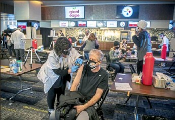 ?? Alexandra Wimley/Post-Gazette ?? Tony Paniele, of McMurray, winces as he receives a dose of the Pfizer-BioNTech COVID-19 vaccine at a clinic organized by Giant Eagle, in partnership with the Steelers, Tuesday at Heinz Field on the North Shore.