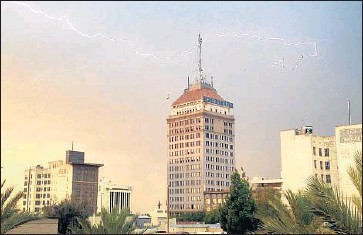 ?? Craig Kohlruss Fresno Bee ?? A lightning strike is seen Saturday over downtown Fresno, one of the many cities to receive rain over the weekend. A reporter continues to come up dry while on a road trip crisscrossing the state.