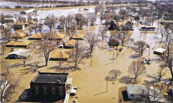 """?? © GETTY IMAGES ?? Below: In Hamburg, Iowa homes and businesses are surrounded by floodwater on March 20, 2019 during some of the worst flooding they experienced in decades. Rain and snow melt from the recent """"bomb cyclone"""" inundated rivers and streams."""