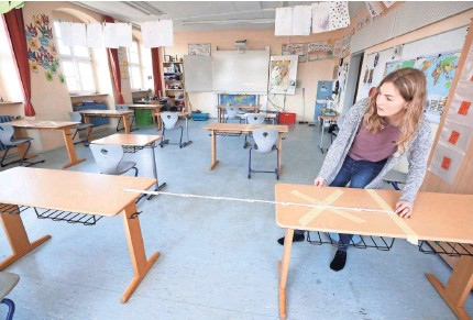 ?? ALEX GRIMM/GETTY IMAGES ?? Staff tape off distanced markings during preparations for reopening a temporarily closed elementary school last week in Heppenheim, Germany. Precautions will accompany the resumption of classes there.