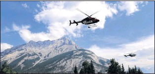 ?? CP PHOTO ?? Helicopters are seen leaving a fire base for the Verdant Creek wildfire in an undated Parks Canada handout image.