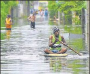 ?? AFP ?? Residents make their way through floodwaters after heavy rains on the outskirts of Colombo on Sunday.