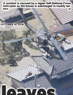 ?? AP ?? A res­i­dent is res­cued by a Ja­pan Self-De­fense Force heli­copter as the house is sub­merged in muddy wa­ters.