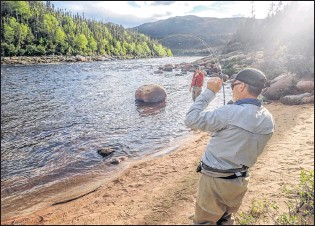 ?? PAUL SMITH PHOTO ?? Rod Hale fighting a fish. Do you see those flies buzzing about his head? You need shelter from them.