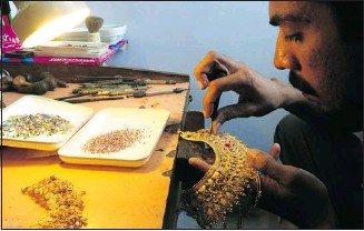 ?? Asif Hassan, AFP-Getty Images ?? A jeweller makes a gold necklace in Karachi on Wednesday, when gold prices rose to historic levels.