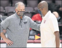 ?? MATT GENTRY/THE ROANOKE TIMES ?? Virginia Tech coach Mike Young (left) and Radford coach Mike Jones talk after the Hokies' season-opening home win. Young said he didn't like the atmosphere created by COVID-19 restrictions.