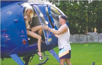 ?? PUBLIC RELATIONS CANADA ?? A screen grab from a promotional video shows a bikini-clad woman getting out of a helicopter at an Anmore mansion for a party. The Anmore mayor is furious the party was held in his community.
