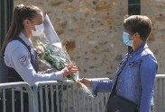 ?? Michel Euler / Associated Press ?? A woman hands flowers to an officer where a police official was fatally stabbed in Rambouillet, France.