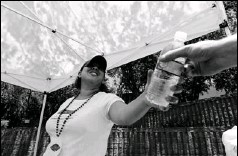 ?? By Robert Hanashiro, USA TODAY ?? Keeping cool: Julie De Anda hands out water in Phoenix, where the high temperatures of 100-101 degrees this week are actually about 7 degrees below normal.