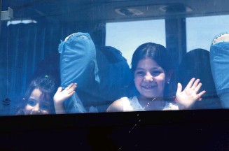 ??  ?? Refugees wave through a bus window as they prepare to cross into Syria at the Lebanese border crossing of Masnaa.