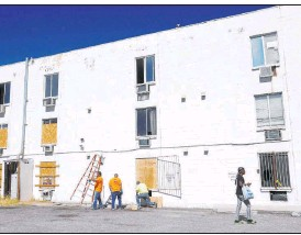 ?? K.M. Cannon Las Vegas Review-journal @Kmcannonph­oto ?? Workers board up windows Oct. 15 at the Alpine Motel Apartments building in downtown Las Vegas. The Alpine, built in 1972, had a history of fire code violations.
