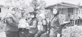 ??  ?? BANTU: Haliza (kiri) menyampaikan sumbangan berupa tuala wanita kepada golongan wanita yang juga penduduk kampung di Kuala Tatau.