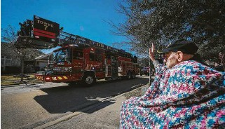 ?? Photos by Capt. Daniel Arizpe, PIO / Cy-Fair Fire Department ?? Cyril Bell — who served as a commando in the British Army from 1939 to 1946 — waves to the crew on Tower 7 ladder truck from the Cy-Fair Fire Department, part of the birthday parade for him.