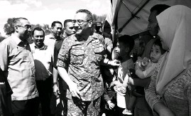 ??  ?? Communications and Multimedia Minister Datuk Seri Dr Salleh Said Keruak with Defence Minister Datuk Seri Hishammuddin Tun Hussein meeting villagers during a combat demonstration by Malaysian Armed Forces at Kem Paradise in Kota Belud yesterday.