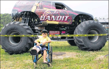 ?? BETH PENNEY/THE TELEGRAM ?? Braiden Benmore in front of the Scarlet Bandit monster truck outside the Janeway hospital in St. John's Friday. He even got the Bandit's driver, Dawn Creden, to sign his cast.