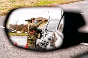 ?? MARK HUMPHREY / AP ?? A National Guard soldier directing drivers is reflected in the mirror of a car waiting in a vaccination line in Shelbyville, Tenn. Tennessee has continued to divvy up doses based on how many people live in each county.