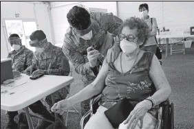 ?? MARTA LAVANDIER/AP PHOTO ?? Loida Mendez, 86, gets the first dose of the Pfizer COVID-19 vaccine March 3 from U.S. Army medic Luis Perez, at a FEMA vaccination site at Miami Dade College in North Miami, Fla. Thousands of older Americans are spending hours online or enlisting their grandchildren's help to sign up for a COVID-19 vaccine. An untold number of older people are getting left behind in the desperate dash for shots because they are too frail, overwhelmed, isolated or poor to navigate a system that favors healthier individuals with more resources.