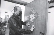 ?? XINHUA ?? Iraqi lover of Chinese culture Mohammed Talib sticks a Chinese calligraph­y fu on his door to offer a blessing and express his wishes of happiness to all Chinese during the recent Spring Festival.