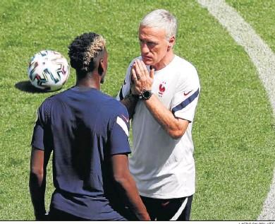 ?? LASZLO BALOGH / EFE ?? El seleccionador francés, Didier Deschamps, conversa con Pogba durante un entrenamiento en Budapest.