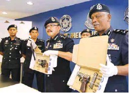?? MASRY CHE ANI/ THESUN ?? Abdul Rahimi (left) and Mazlan showing the seized guns during a press conference in Northeast district police headquarters yesterday.