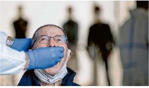 ?? Foto: Marijan Murat/dpa ?? Einem Mann wird an einer Corona-Abstrichstelle auf dem Cannstatter Wasen eine Probe entnommen.