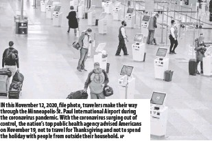 ?? AP ?? In this Novem­ber 12, 2020, file photo, trav­el­ers make their way through the Min­neapo­lis-st. Paul In­ter­na­tional Air­port dur­ing the coron­avirus pan­demic. With the coron­avirus surg­ing out of con­trol, the na­tion's top pub­lic health agency ad­vised Amer­i­cans on Novem­ber 19, not to travel for Thanks­giv­ing and not to spend the hol­i­day with peo­ple from out­side their house­hold.